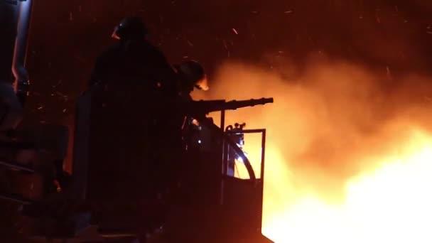 Silueta hasiče s jasnými plameny v pozadí