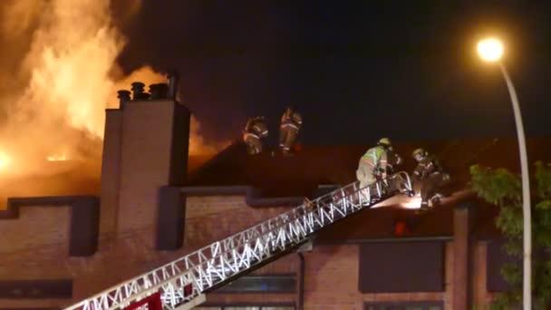 Hasiči stojící na střeše v blízkosti těžkých plamenů