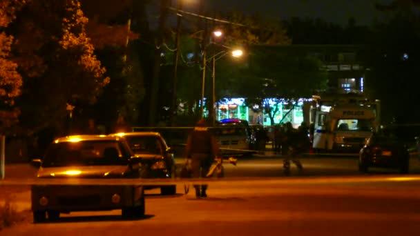 Policisté SWAT chodí v noci na místo činu se sanitkou.