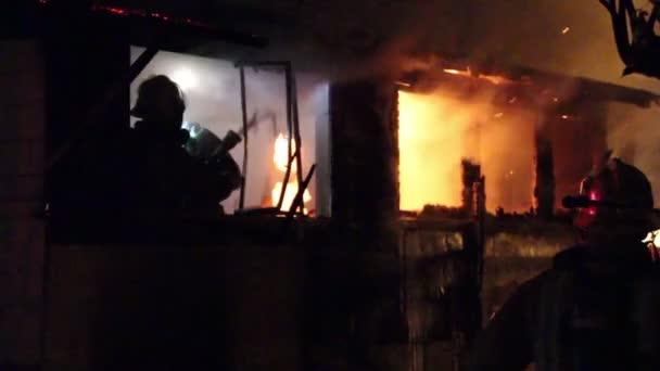 Hasiči bojující v noci s požárem domu s plameny