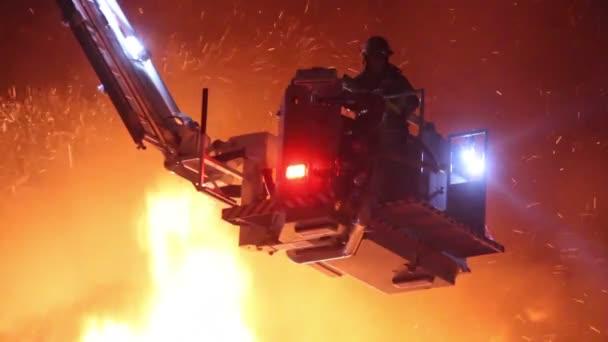 Hasiči v siluetě na plošině hasičského vozu s plameny střílející vysoko