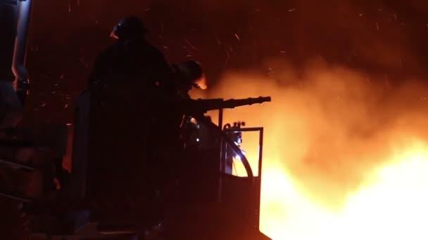 Silueta požárníků v ohni s hadicí a silnými plameny