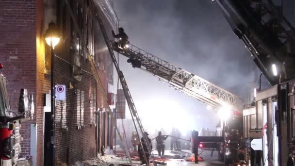 Hasič na vrcholu žebříku směruje obsluhu poblíž požáru budovy