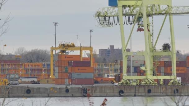 A rakománykikötőben nagy daru alatt haladó platós teherautók