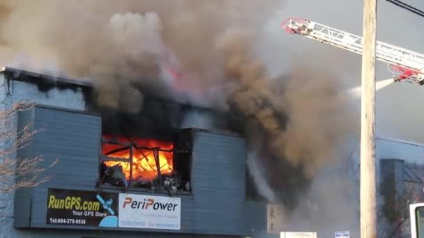 Sűrű szürke füst által létrehozott épület tűz lángok mutatják az ablakon keresztül