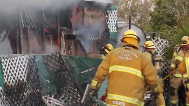 Hasiči bojující s ohněm sekerou a motorovou pilou