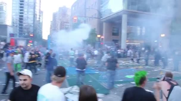 Terrible shot of rioters pushing fence falling on girl talking on the phone