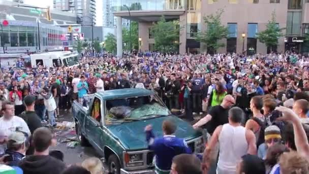 Man attempting to stop thugs kicking and damaging a vehicle in middle of riot
