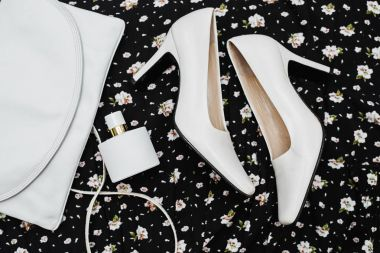 Stylish female accessories. White Shoes with handbag and perfume