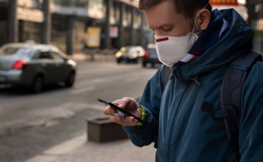 guy in a medical mask on the street uses a smartphone
