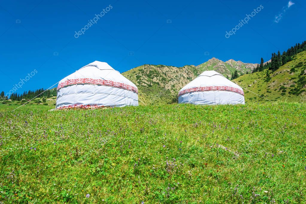 Two white yurts in the mountains of Kyrgyzstan.