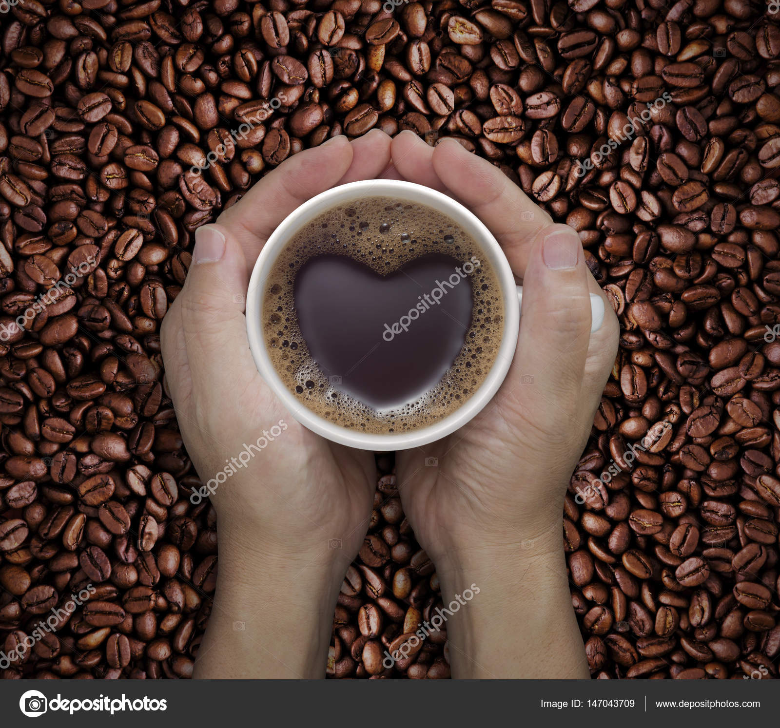 Love Coffee Cup In Hands With Heart Shape On Bean Stock Photo