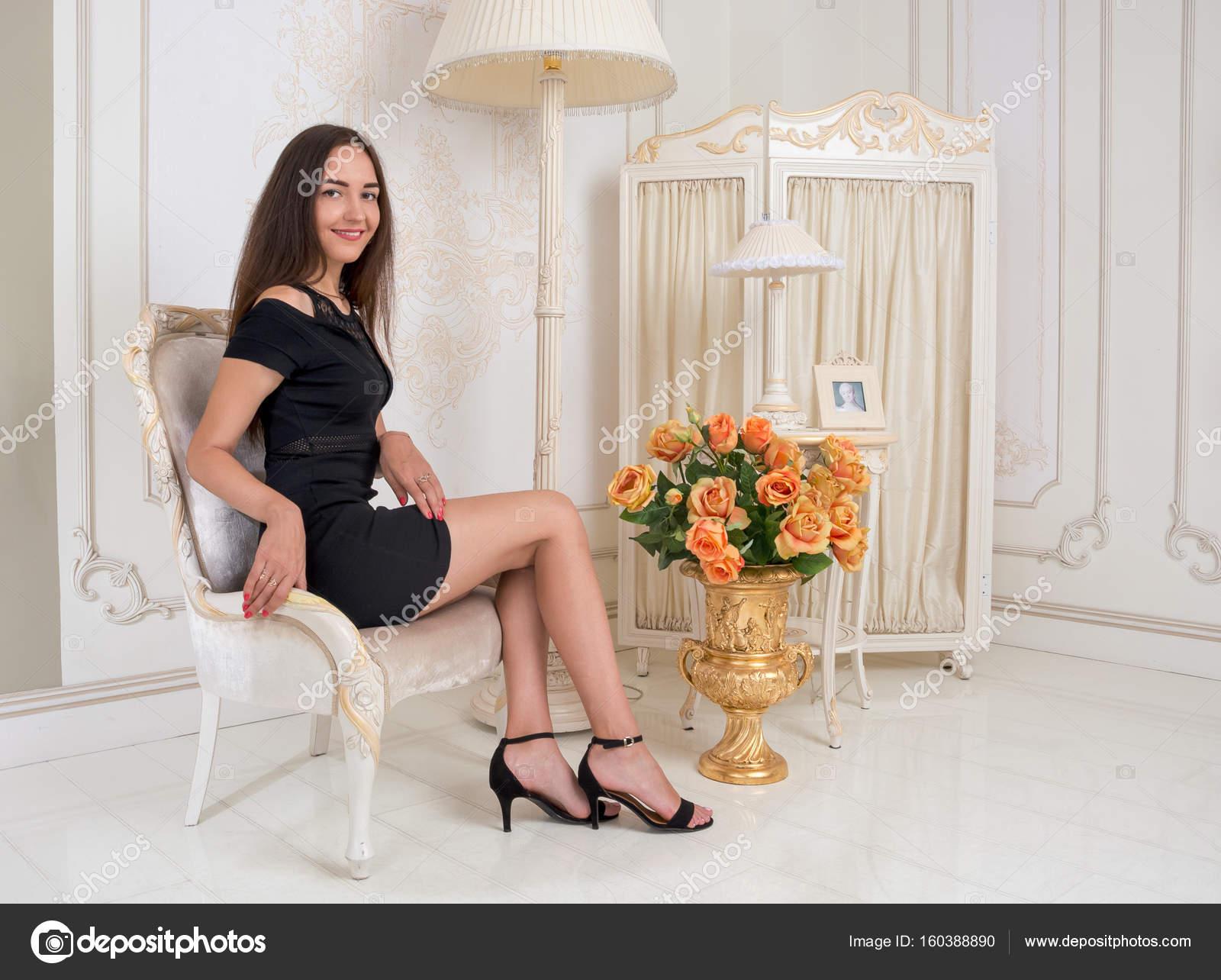 3670d621b79f Νεαρή γυναίκα με ένα κοντό μαύρο φόρεμα που κάθεται σε μια καρέκλα μπροστά  o — Φωτογραφία