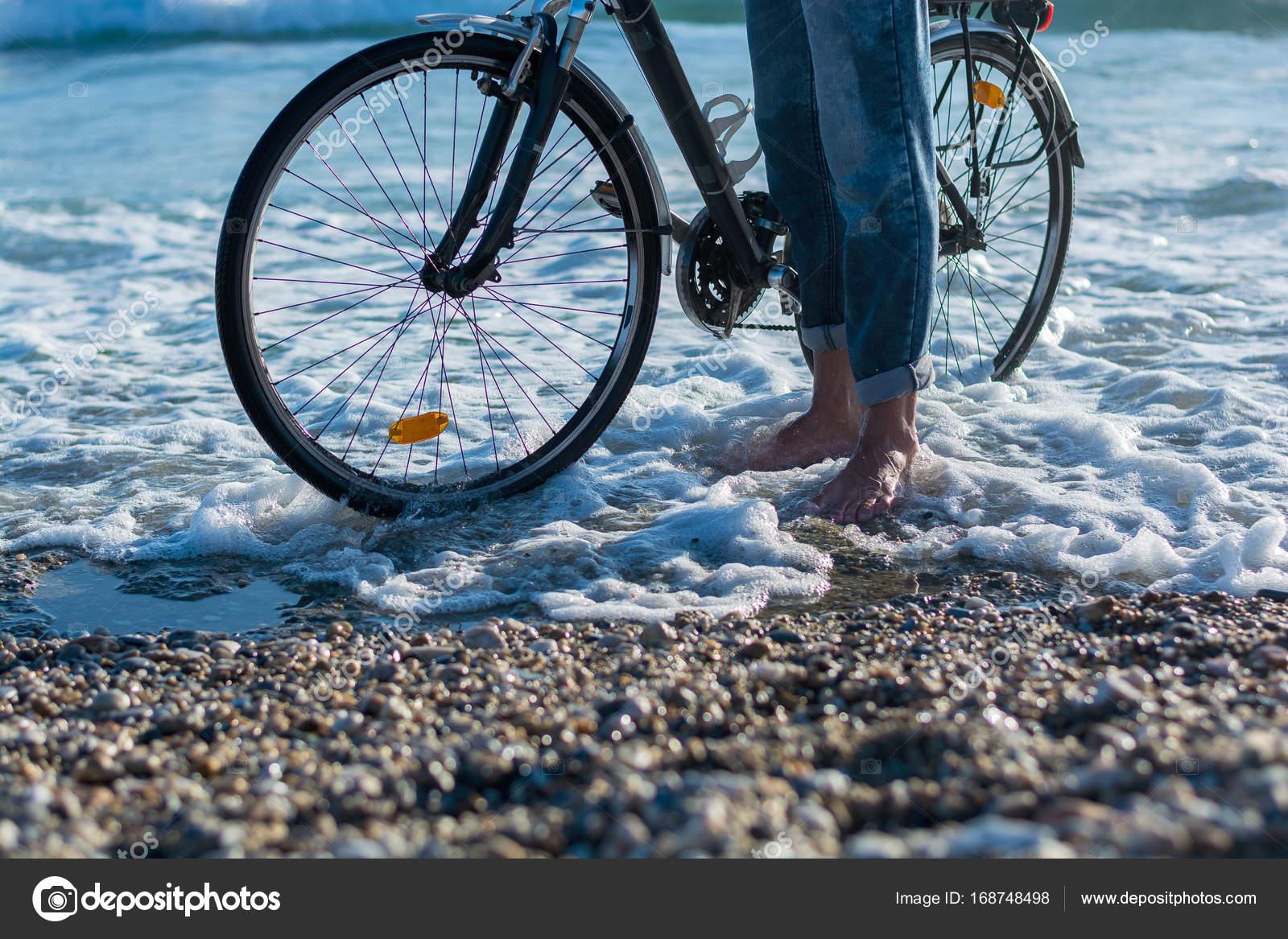 Le Gambe Di Un Uomo Che Cammina Con Una Bicicletta Lungo La Riva Del