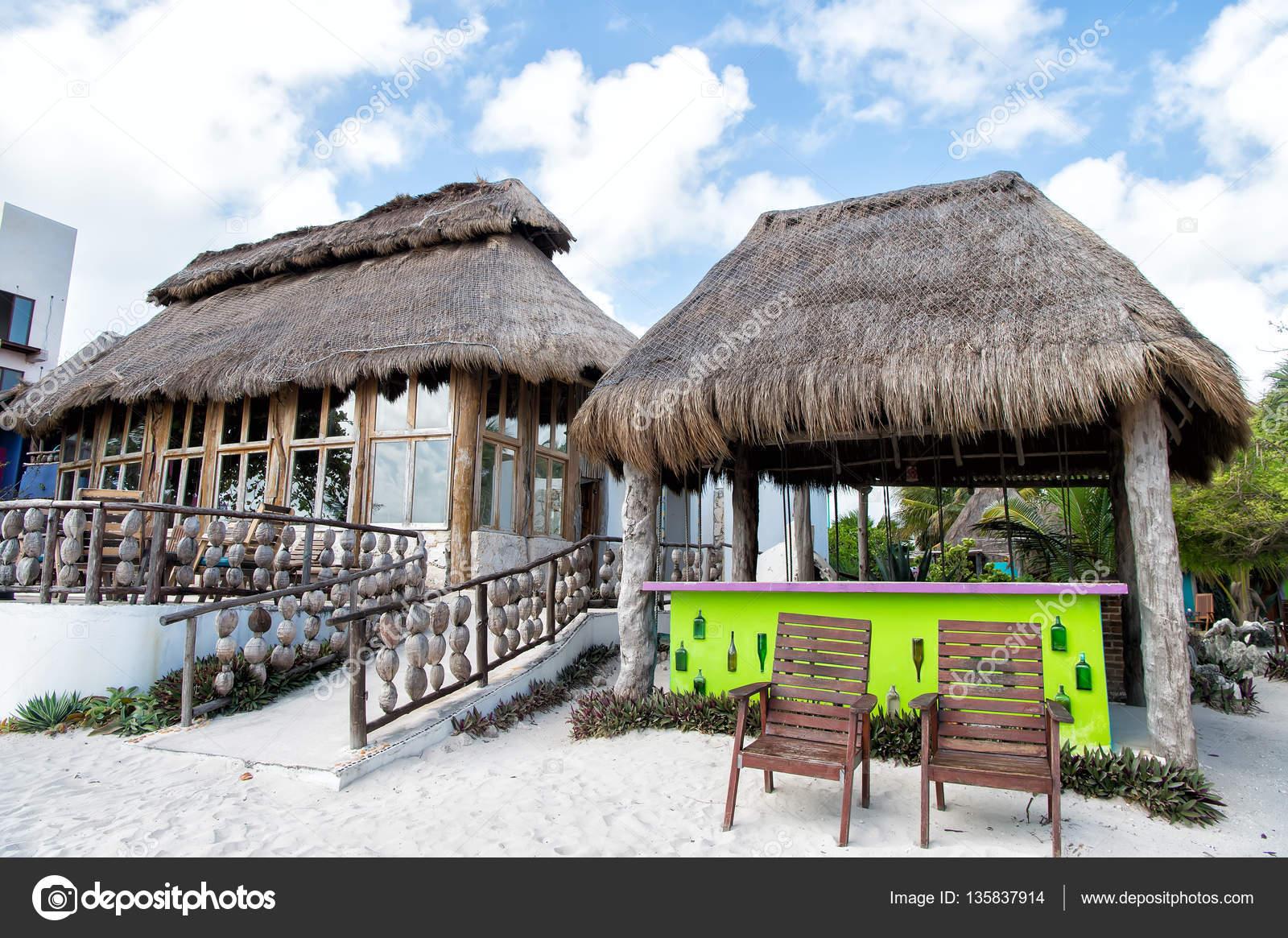Bar de praia exótica com construção de casa e telhado de palha perto de  cadeiras na areia ao ar livre em fundo azul céu nublado — Fotografia por  stetsik 9863b8fc770
