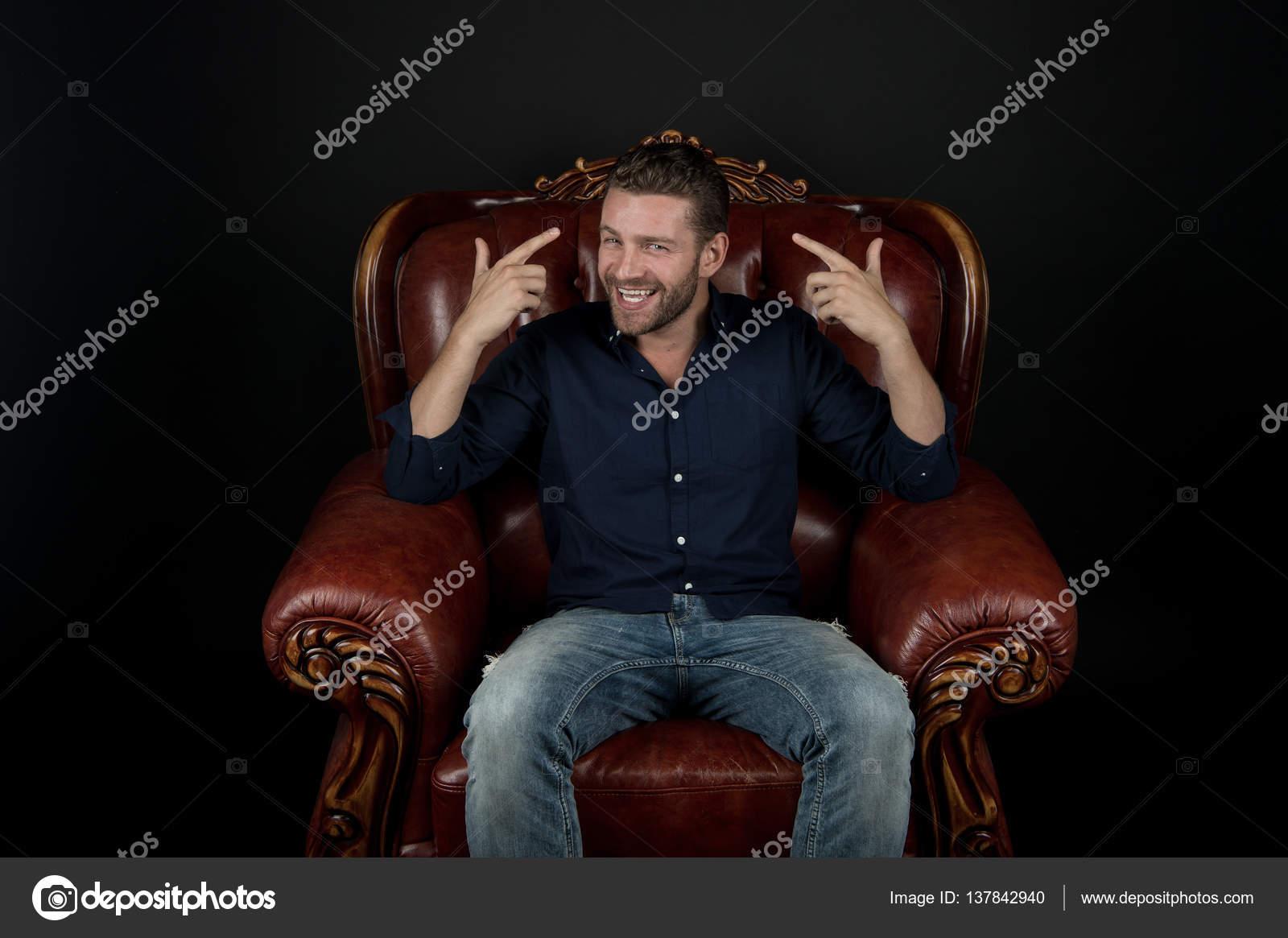 Uomo barbuto felice in sedia in pelle foto stock for Sedia design faccia