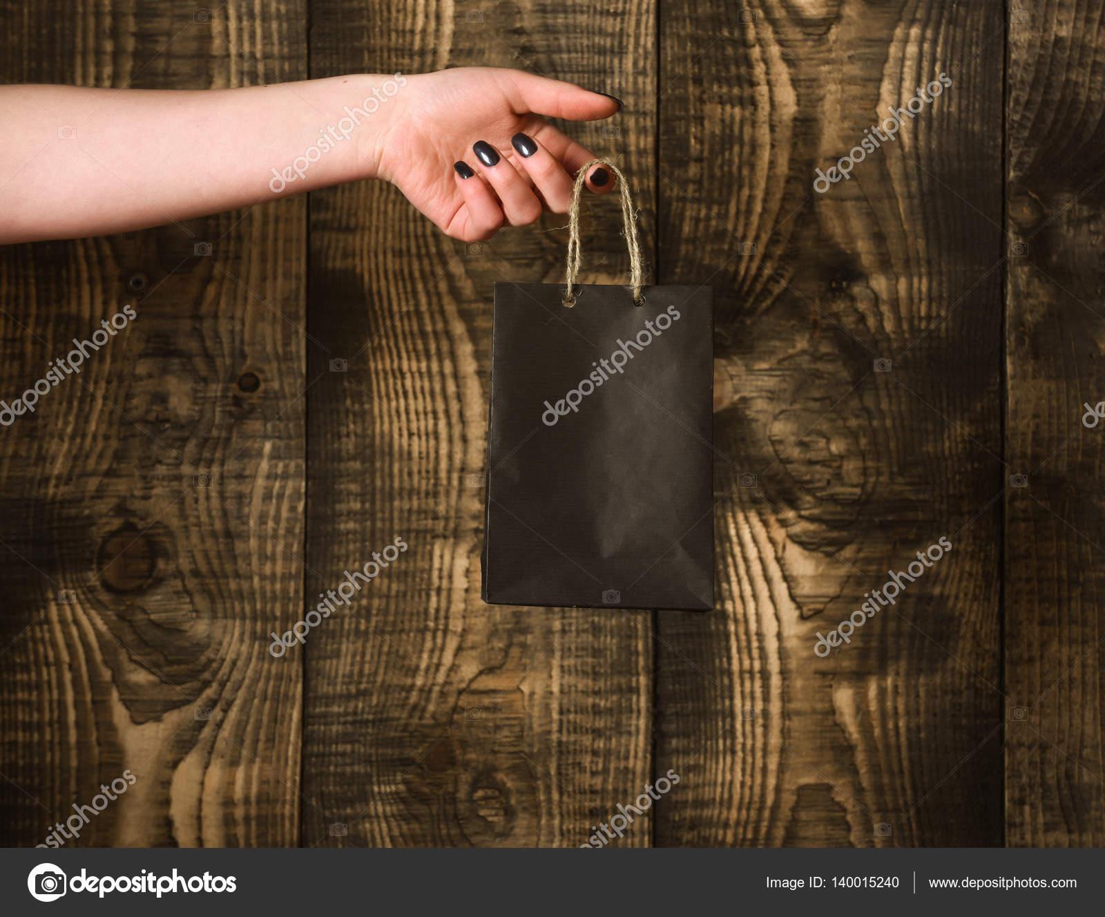 Bolso de compras negro en mano mujer sobre fondo de madera
