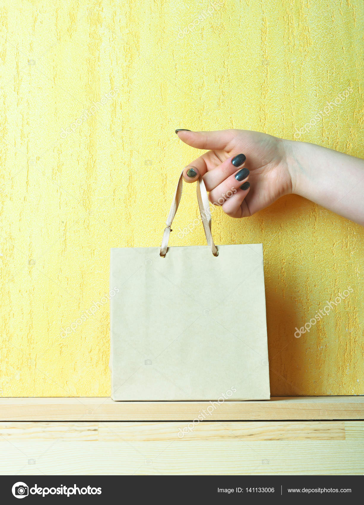 light blue shopping bag in female hand on yellow wall — Stock Photo ...