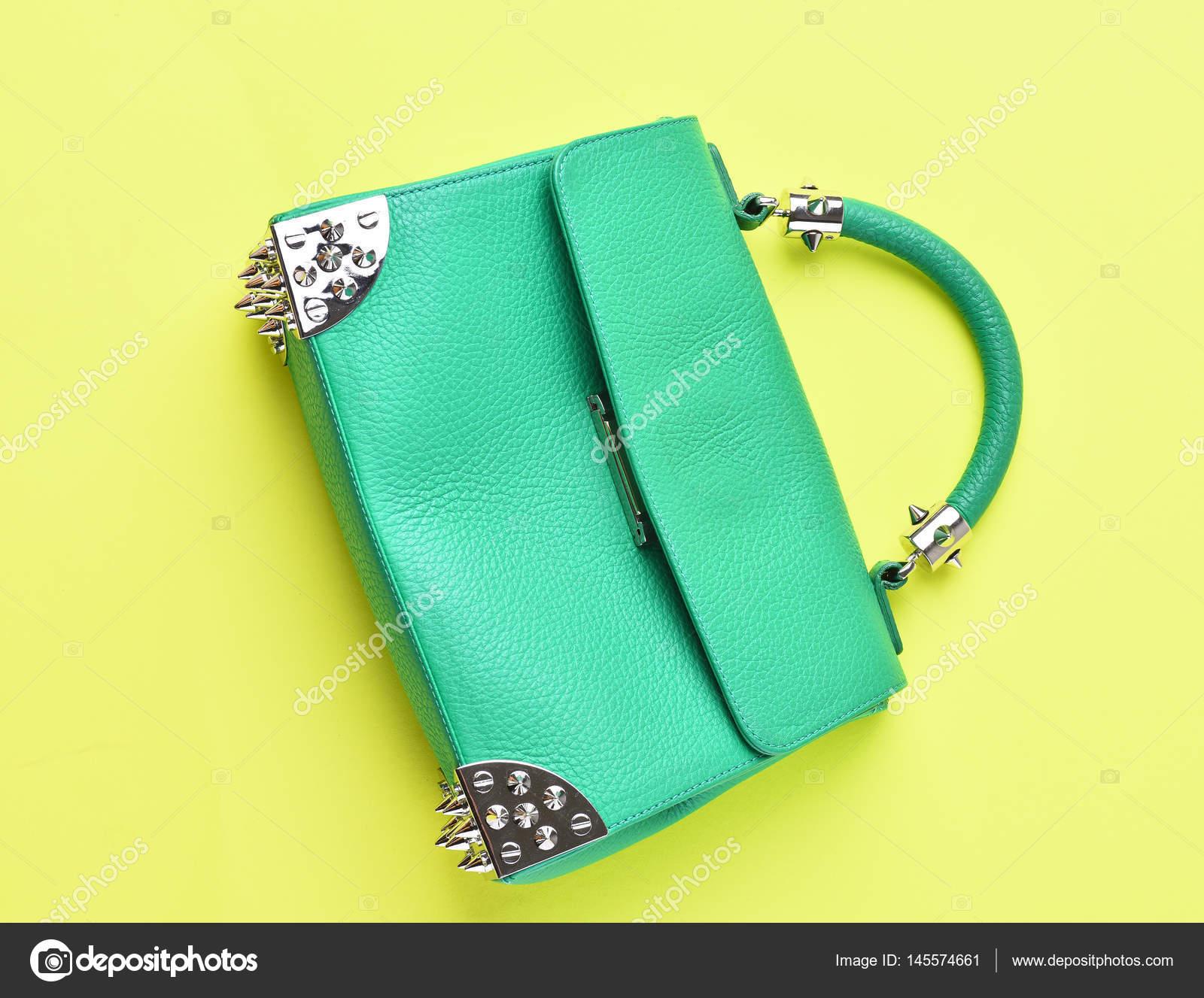 4081e59ba7 Ωραία όμορφη μικρή γυναικεία δερμάτινη πράσινη μοντέρνο τσάντα με διακοσμητικό  μεταλλικό αιχμές ή αγκάθια σε κίτρινο φόντο — Εικόνα από ...