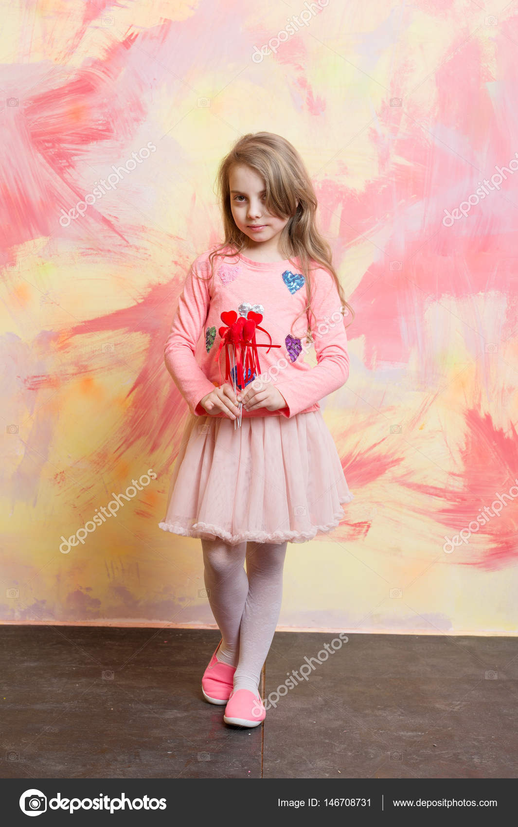 small baby girl holding valentines day decorative red hearts — stock