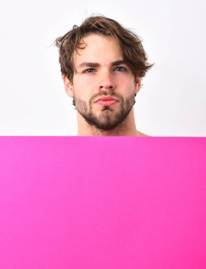 Caucasian sexy young macho holding fuchsia or pink paper sheet