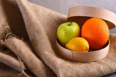 various fruits: lemon, apple, orange on sackcloth napkin