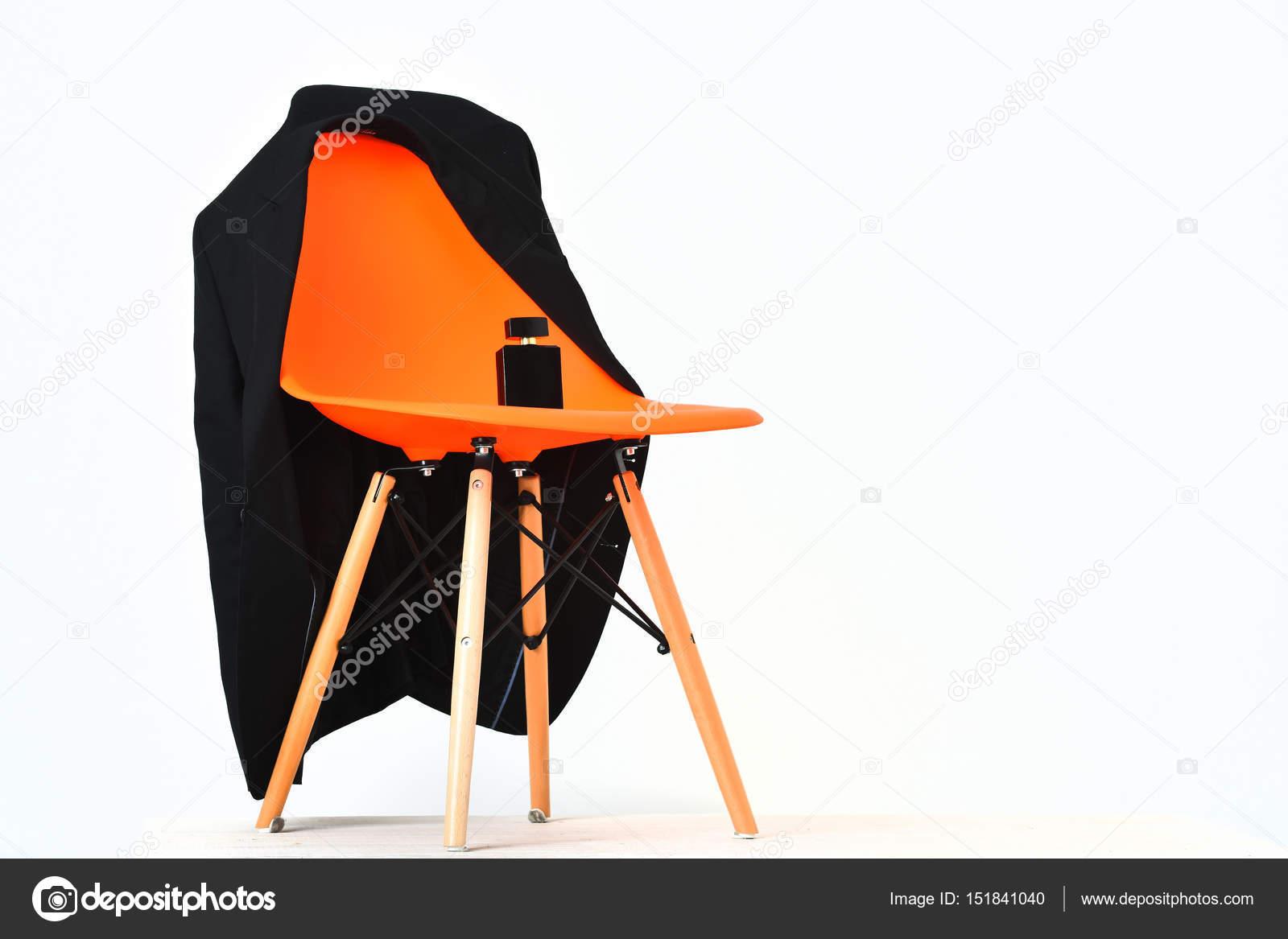 Chaise de bureau en plastique orange avec bouteille noire veste et
