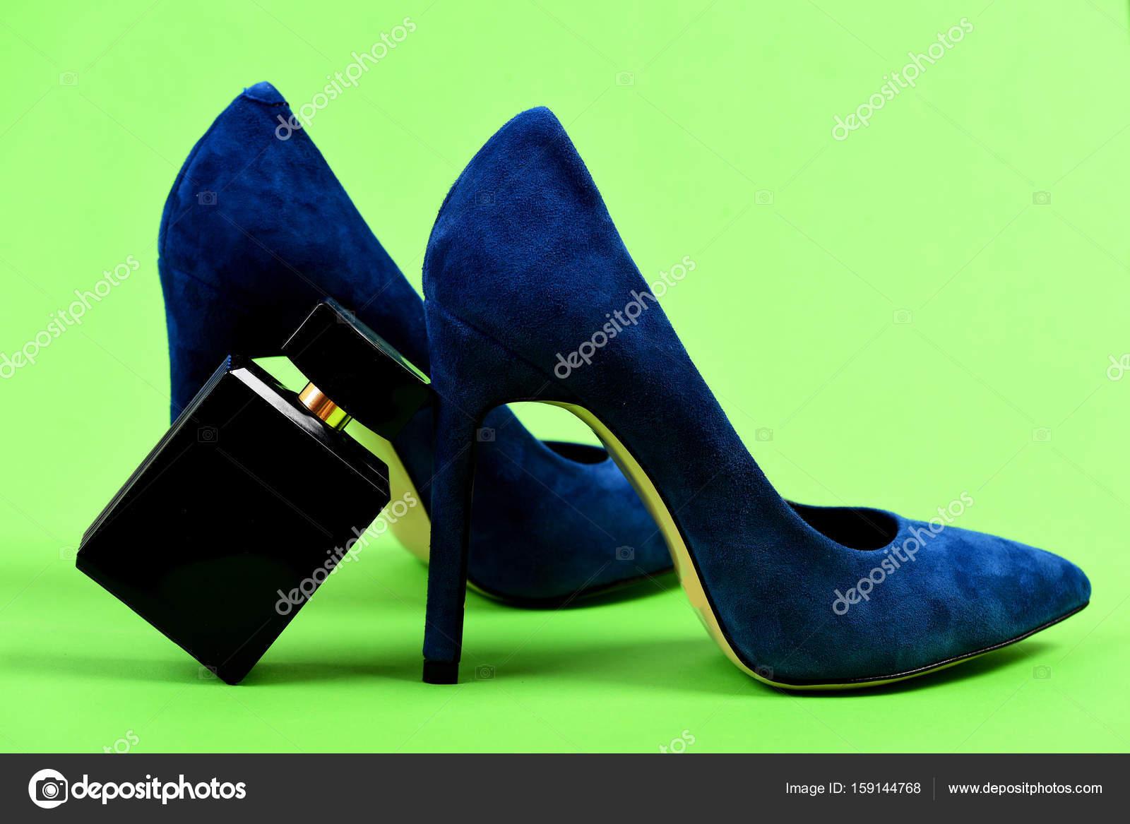 Scarpe in blu scuro con la bottiglia di profumo. Paio di scarpe donna  camoscio fantasia e accessori. Scarpe tacco alto isolato su sfondo verde  chiaro. 39ae6d8bfc0