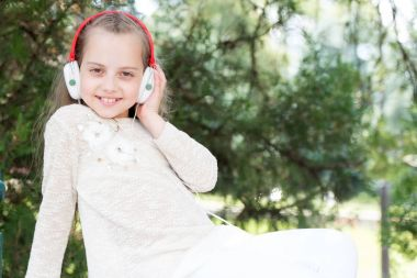 Pretty little girl enjoying music using headphones