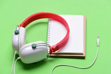 Headphones in white and red color with empty notebook