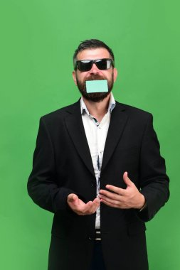 Guy with funny face and sunglasses isolated on green background