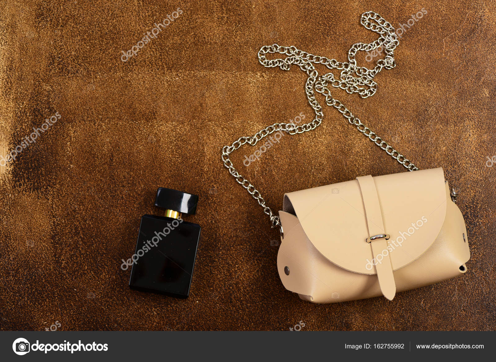 119f6b7d03 Μπεζ τσάντα με μεγάλη μεταλλική αλυσίδα. Μόδα και άρωμα έννοια. Δερμάτινο  τσαντάκι και Άρωμα μπουκάλι σε φόντο καφέ σουέτ. Γυναικεία αξεσουάρ