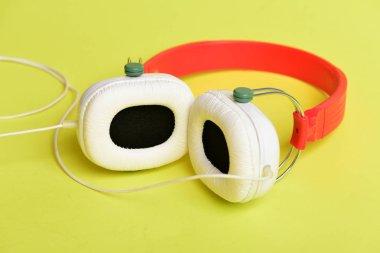 Modern and stylish earphones isolated on yellow background