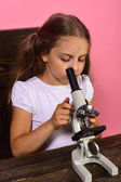 Schoolgirl with concentrated face looks into microscope and does experiment