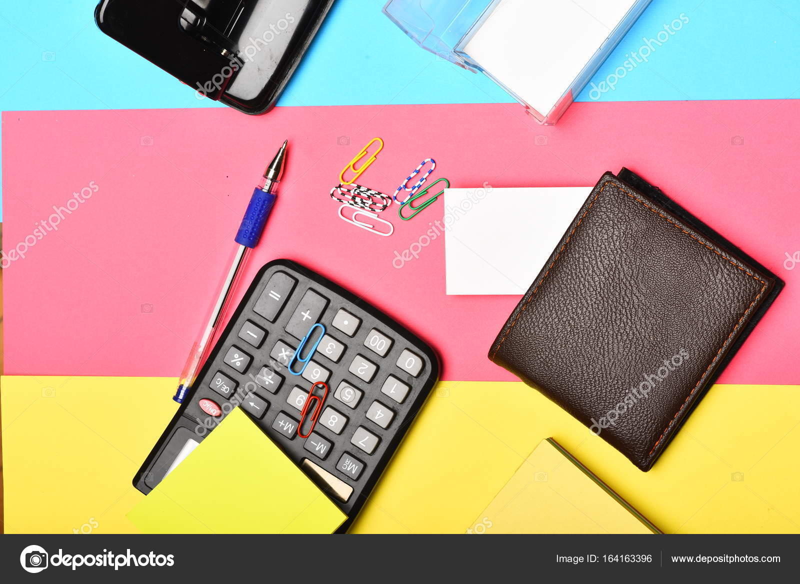 Calculator, hole punch, business card holder on colourful backgr ...
