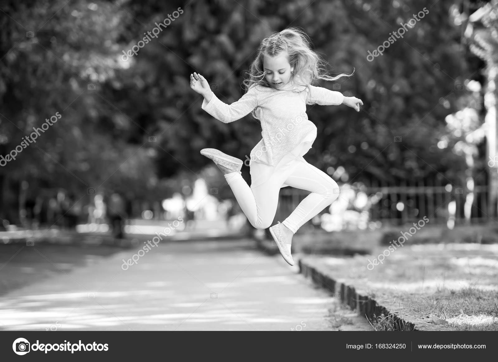 f26208ea Pretty little girl with curly blonde hair jumping on street — Stock Photo