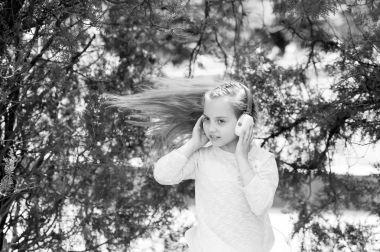 Cute little girl enjoying music using headphones