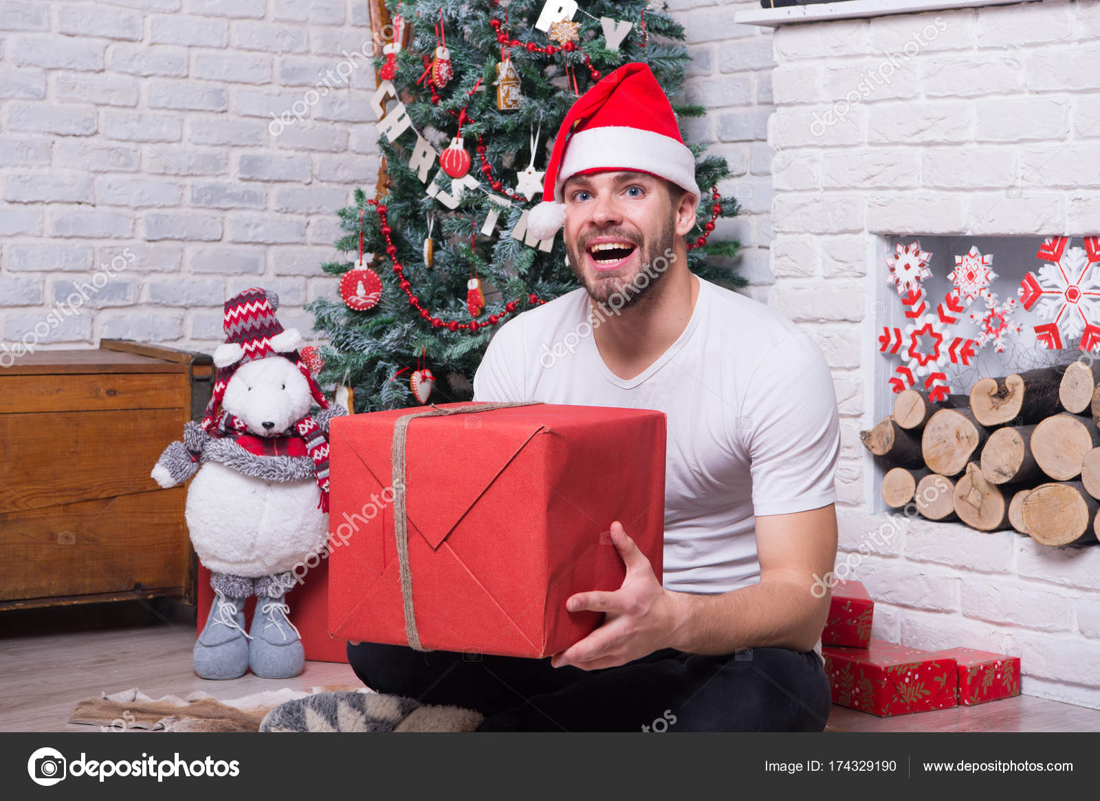dbceda4aecba5 Man in santa hat sit on floor at fireplace. Macho smile with present box