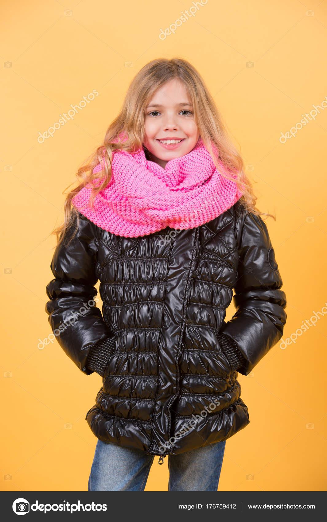 00059e6fced Κορίτσι σε μαύρο παλτό και ροζ φουλάρι σε πορτοκαλί φόντο. Παιδί ομορφιά,  κοιτάξτε, χτένισμα. Φθινοπωρινή μόδα, το στυλ, η τάση. Έννοια ευτυχισμένη  παιδική ...