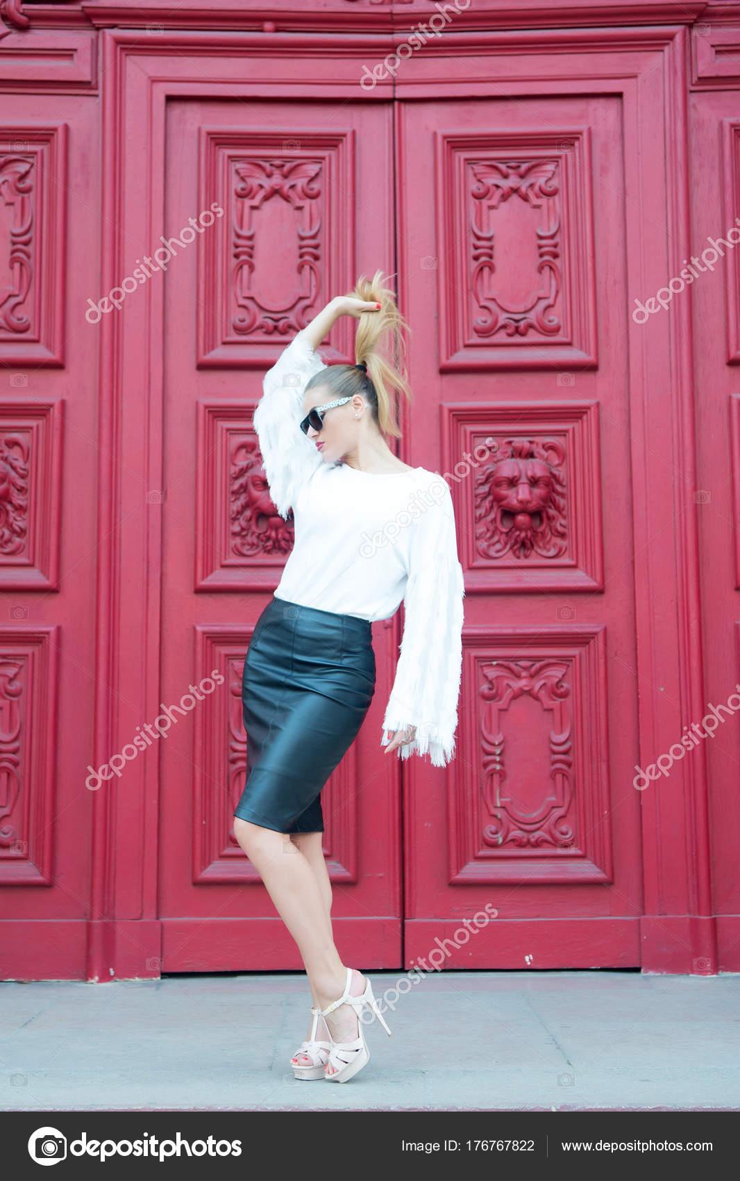 Femme Avec Queue De Cheval Cheveux Blonds Sur La Porte Rouge à Paris