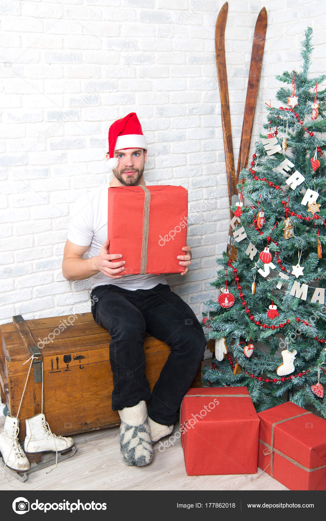 a6ae6563a1538 Macho in red hat hold wrapped present. Gift giving and exchange. Man santa  with boxes at christmas tree. Boxing day concept.