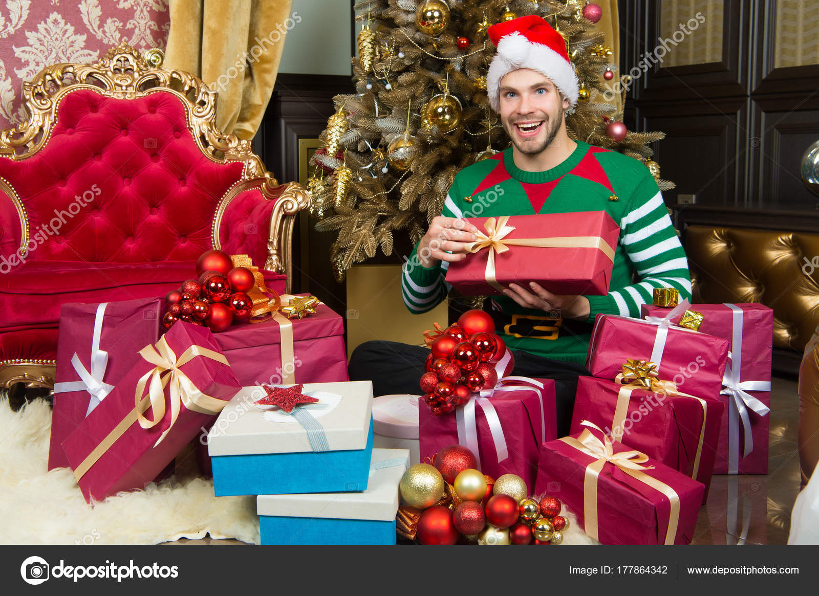 583196836e8dd Macho in elf costume prepare gift boxes. Man in santa hat smile with  presents at Christmas tree. Holidays preparation