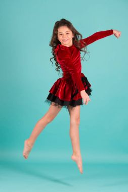 Little girl dancer jump on blue background. Child dance in red dress barefoot. Happy childhood concept. Performance, ballet, gymnastics, activity, energy. Grace, beauty, fashion. Punchy pastel trend.