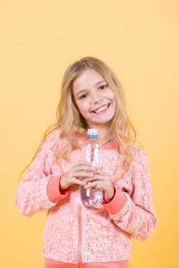 Happy child with drinking water. Girl smile with water bottle on orange background. Drink healthy water. Life source concept. Nutrition, healthcare, lifestyle, punchy pastel.