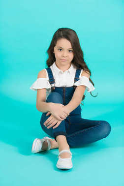 Child model in jeans overall sit on floor