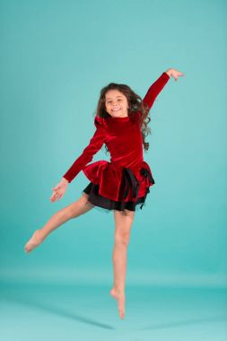 Child dance in red dress barefoot