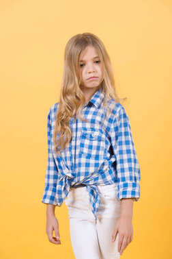 Child pose in shirt and pants on orange background