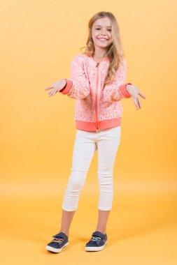 Small girl smile in sweatshirt, pants, sneakers, fashion