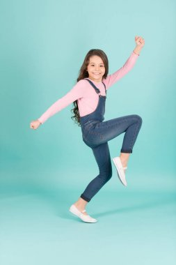 Happy child in jeans overall dance, fashion