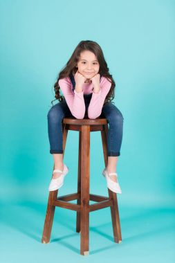 Small girl in jeans overall sit on chair, fashion